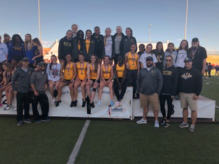 Girls track team and coaches pose after their Area win.