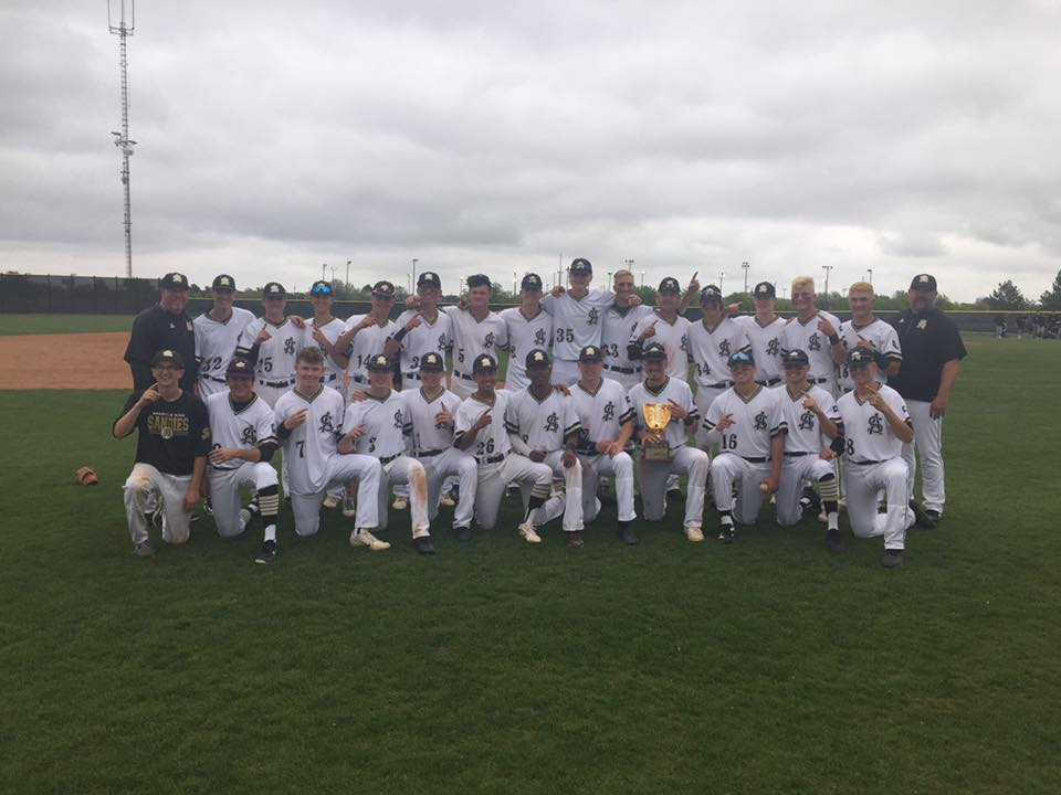 Baseball team poses with their Bi-District trophy.
